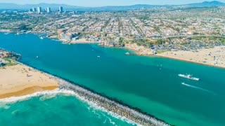 4K aerial footage from a drone over The Wedge surfing spot in Newport Beach with the harbor entrance, Corona Del Mar, Fashion Island, blue skies and coastal homes in the background.