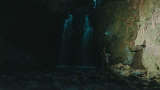 4K Aerial of Man and Woman Doing Photo Shoot Next to Waterfall
