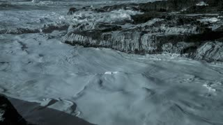 4K Aerial Slow Mo Flying Over Foaming Waves Crashing Over Rocky Shore