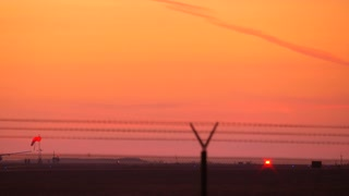 4K footage of twin engine jet plane take off in silhouette against an orange sky sunset with sound