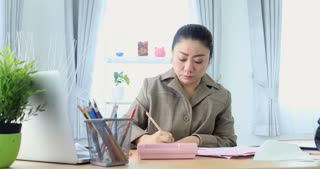 4K Portrait of Asian woman working hard about paying the bills