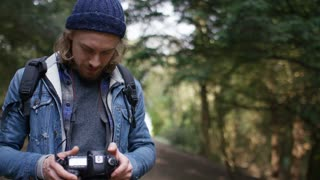 4K Portrait of photographer in the forest smiling to camera, in slow motion