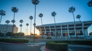 4K time lapse in motion (hyper lapse) with a gorgeous sunset palm trees and corporate buildings in Newport Beach.