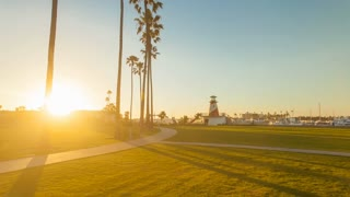 4K timelapse in motion or hyperlapse with a gorgeous sunset at a public park with clouds, palm trees, walking paths and a stunning lighthouse next to the Newport Beach harbor