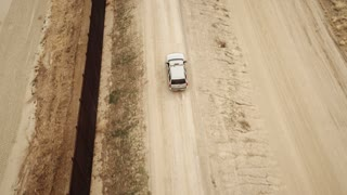 4K UHD Aerial Birds Eye View of Border Patrol Driving Along Wall of Mexico Border