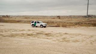 4K UHD Aerial Circling Around Mexican Border Patrol Driving Along Dirt Road