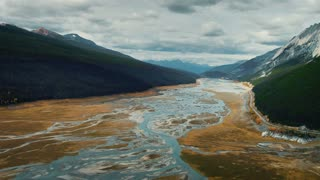 4K UHD Aerial Panning Shot of Streams and Meadow Through Mountains in Jasper National Park