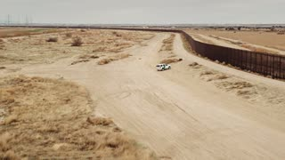 4K UHD Aerial Shot of Border Patrol Driving Up to Wall of Mexico Border