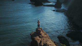 4K UHD Aerial Shot of Woman Photographer Standing On Ocean Cliff