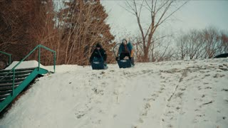 4K UHD Shot of People Riding Sled Down Snowy Hill