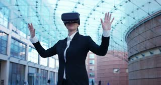 A beautiful career woman uses virtual reality, in the background the business centre. The business woman playing and having fun with augmented reality. Concept: insurance, business,immersive technology