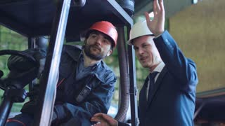 A businessman explaining to the driver the work in the warehouse. Horizontal indoors shot
