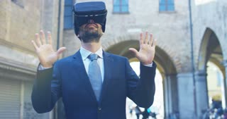 A businessman in a suit uses augmented reality in the city among the people. Concept: immersive technology, augmented reality and futuristic business.