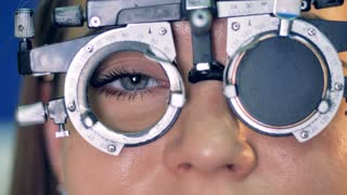 A close-up view on a womans eye behind the optical trial frame.