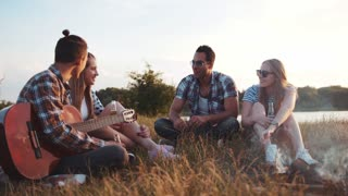 A company of four friends having fun by the fire near the lake, drinking beer, laughing, toasting in bright sunshine. Young man holds the guitar. Having a rest, best friends. Positive emotions.