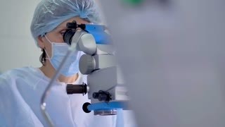 A female surgeon uses a profession microscope station.
