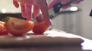 A girl is cooking a salad in the kitchen. She cuts the red juicy tomato into many small pieces.
