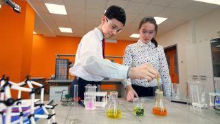 A girl watches a boy mixing chemicals.