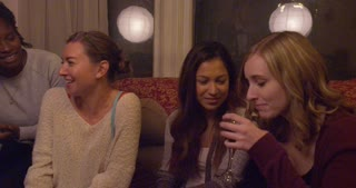 A group of women drink from a glass of wine at a holiday party.