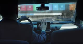 A man driving a technological and futuristic machine in which holograms appear for a driver assistance and video calls. Concept of machines of the future, driving safety, technology and transport