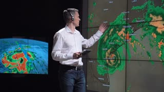 A news weather reporter wearing a headset presenting a live hurricane forecast displayed on two large screens. Elements of this image furnished by NASA