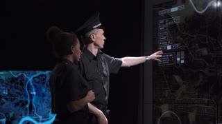 A police coordination team and officers discuss response tactics in front of large live screens in a futuristic office