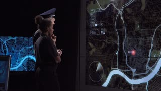 A police coordination team and officers discuss response tactics in front of large live screens in a modern office