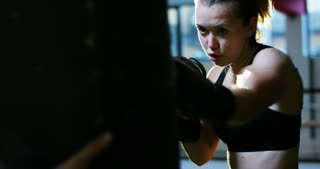 A professional boxer girl in the gym works with a punching bag, a technique of striking, a rack, protection and endurance, black gloves. The concept: love of sport, young boxers, love of victory.