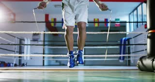 A professional boxer in the gym, jumping rope, improving endurance, speed and sharpness, excellent body and training, in white sportswear. Concept: love of sport, young boxers, love to win