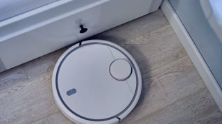 A robotic vacuum moving along white drawers in a smart house. 4K.