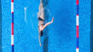 A woman swims in crawl in an open back swimsuit.