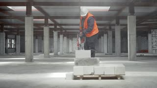 A worker at the construction site saws circular saws concrete block