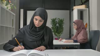 A young beautiful girl in a point and a black hijab will write off in Arabic. Arab women in the office 60 fps