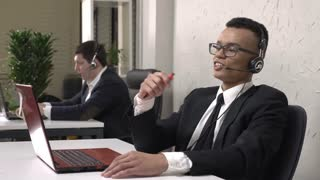 A young successful African man is sitting in the office and talking on the headset, call center concept. Caucasian man in suit in the background. Call center concept. 60 fps