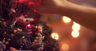 Woman adjusting decorations and ornaments on a glowing Christmas tree - slow motion