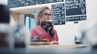 Adorable blonde girl with casual hairstyle and stylish glasses standing by the coffee bar waiting for her order, receives her coffee and gives a bright thankful smile. Cozy café atmosphere.