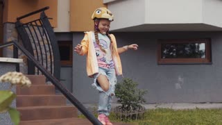 Adorable cute girl in a colorful helmet runs out of the house, sits on her bike, and rides away together with her little brother. Having fun, feeling happy, happy childhood