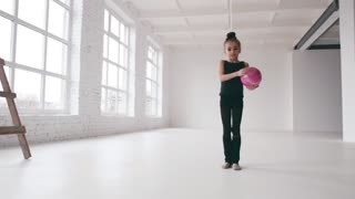 Adorable little girl gymnast dressed in a sport-suit for competition, performs exercises with the pink ball, the ball falls down. Hobby, positive emotions. Having fun, active lifestyle.