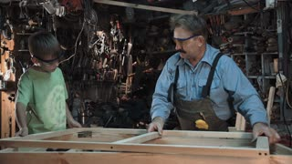 Adult carpenter man and grandson putting element on window and handshaking in workshop