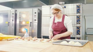 Adult kind smiling woman bakes and forming cakes in the bakery