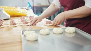 Adult woman bakes and forming meat pies in the bakery