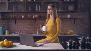adult woman working on the kitchen. Attractive woman using computer drinking tea at home