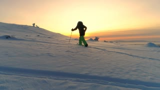 AERIAL: Active woman exploring snowy Lapland wilderness on snowshoes at sunrise