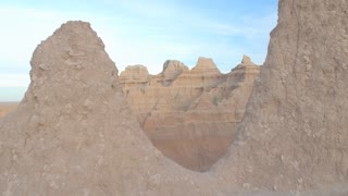 AERIAL: Amazing pointy sandstone mountains against clear blue sky in Badlands NP