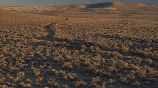 AERIAL: Black SUV car driving through volcanic bushy desert in sunny evening