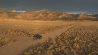 AERIAL Black SUV car traveling on dirt road towards majestic Rocky Mountains