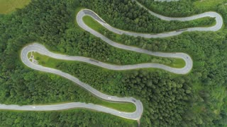 AERIAL: Cars driving on mountain along scenic switchback road with hairpin turns