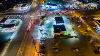 Aerial cinematic timelapse in motion or hyperlapse looking at an urban intersection showing the busy city traffic at rush hour from above.