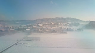 AERIAL: Cute small countryside town surrounded by snowy fields in misty morning