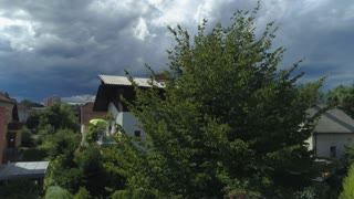 AERIAL: Dark stormy clouds above house rooftops in beautiful green suburban town